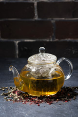 fresh tea in a glass teapot on dark background, vertical