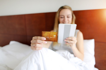 focus on credit card hold by young australian woman with tablet in white bed sunshine