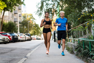 Athletic mixed race couple running outdoors
