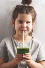 Beautiful happy little girl drinking healthy green vegetable-fruit smoothie. Healthy children vegan food concept.