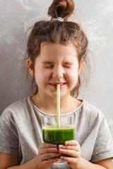 Beautiful happy little girl drinking healthy green vegetable-fruit juice. Healthy children vegan food concept.