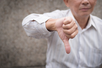 angry senior giving thumb down gesture, unhappy upset frustrated old man