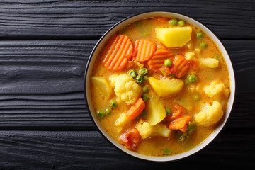 Vegetarian curry from vegetables with coconut milk close-up in a bowl. Horizontal top view