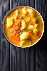 Vegetarian curry from vegetables with coconut milk close-up in a bowl. Vertical top view