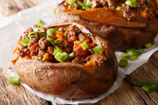 Organic food: baked sweet potato stuffed with ground beef and green onion close-up on paper. horizontal