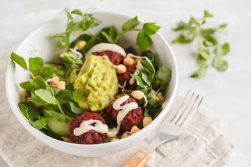 Green vegetable vegan salad with beets meatballs, Guacamole and tahini dressing. Healthy vegetarian food concept. Copy space