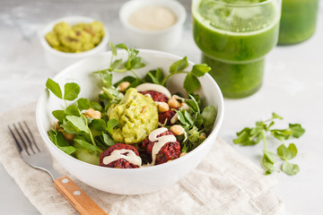 Green vegetable vegan salad with beets meatballs, Guacamole, tahini dressing and green juice. Healthy vegetarian food concept.