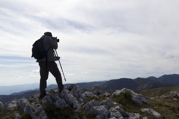 silhouette hiker take photo on mountain peak