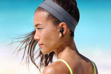 Wireless earbuds woman listening to music on beach