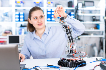 A girl in a University laboratory is experimenting with a robot