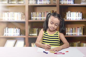 Happy asian little girl drawing on paper with crayon