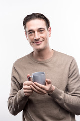 Love this drink. Pleasant handsome man holding a small cup of coffee in his both hands and smiling pleasantly, while posing isolated on a white background