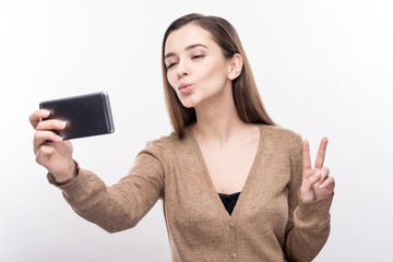 Loving myself. Adorable young woman showing a V sign and taking selfies while posing isolated on a white background