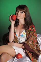 beautiful brunette in russian scarf with apples in studio