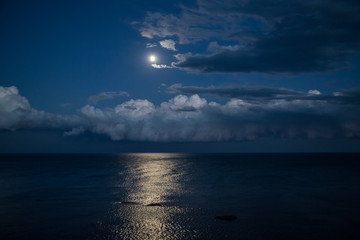 Night sky with full moon and reflection in sea.
