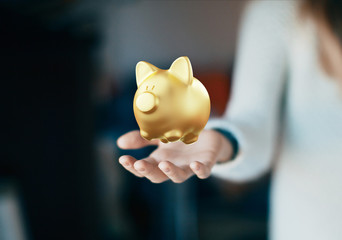 Mano con porcellino salvadanaio d'oro, risparmio o investimento