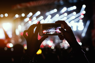 Hands with a smartphone records live music festival, Taking photo of concert stage