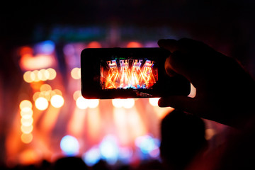 Hand with a smartphone records live music festival and taking photo of concert stage.