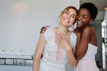 Cheerful bride and bridesmaid on the wedding day