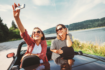 Two female freinds take a selfie photo during their auto travel