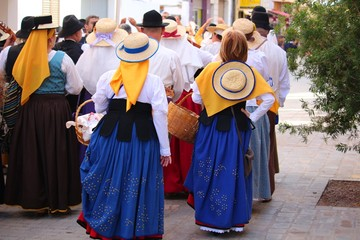Locals in traditional dresses enjoy singing at a public festival in San Sebastian, La Gomera Wall mural