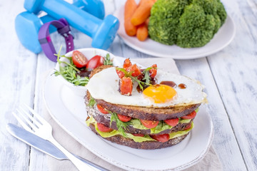 Toast from a grain bread with cheese and tomatoes and egg. Vegetarian food. on a white plate and blue dumbbells and a fitness bracelet for fitness. Useful breakfast. Free space for writing text.