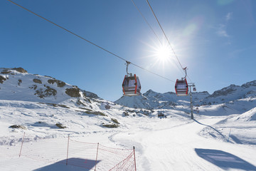 Cableway lift cable cars, gondola cabins on winter snowy mountains background beautiful scenery.