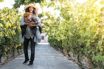 happy young interracial couple on holiday in a vineyard.