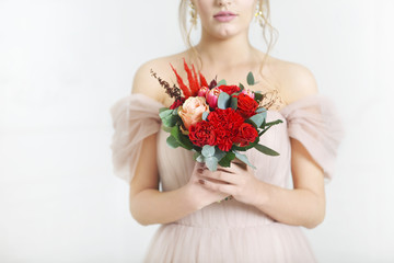 Young pretty bride with bridal bouquet indoors