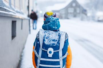 Happy kid boy having fun with snow on way to school