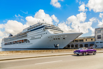 Big cruise ship docked in port of Havana and road with retro old car, Cuba