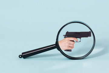 Gun handle throw Magnifying glass, on a pastel blue background