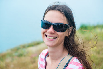 Woman 25-30 in sunglasses stands on the hill. Closeup portrait. Brunette with long hair, smiling.