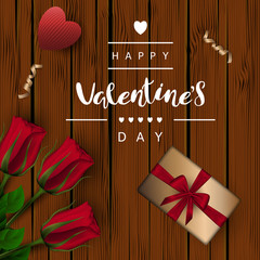 "A square brown wooden board background with red buds of roses on a green stem and gift boxes with a bow, a knitted heart, a golden ribbon. Festive inscription of the lettering ""Happy Valentine's Day"""