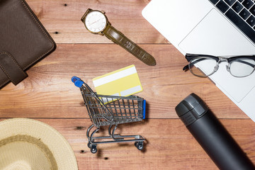 Credit card, watch, smartphone and coffee cup on wooden table