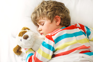 little blond kid boy in colorful nightwear clothes sleeping