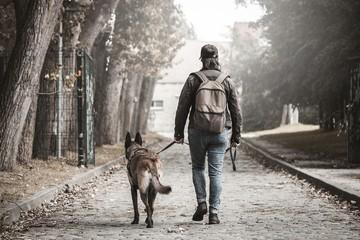 Femme avec un malinois. Post apocalypse. voyager à pied avec son chien. Femme qui marche sur un chemin de pierre avec un sac à dos.Femme qui se dirige vers le bâtiment au bout de la route.