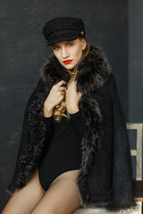 portrait of attractive lady in a black cap and a sheepskin coat with a fur collar . Perfect makeup, red lips and blue eyes