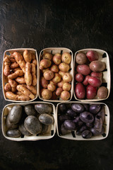 Variety of raw uncooked organic potatoes different kind and colors red, yellow, purple in market baskets over dark texture background. Top view, space