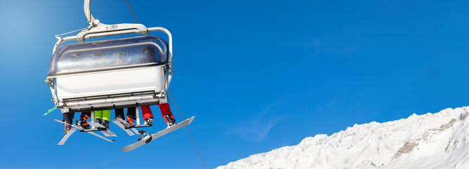 skiers and snowboarders in a ski lift against clear blue sky. blank space for text
