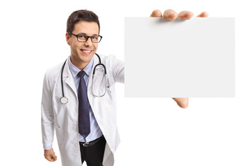Young doctor showing a blank card