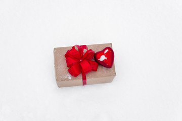 gift tied with a red bow and heartgift on white background/ snow