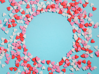 Candies hearts of pastel colors on blue paper. Flat lay.