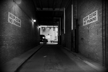New York, a road tunnel with writings on the walls and vehicles at the end. Black and white urban landscape.