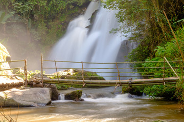 Waterfall flowing down the creeks, which a wooden bridge made out of bamboo used to walk across