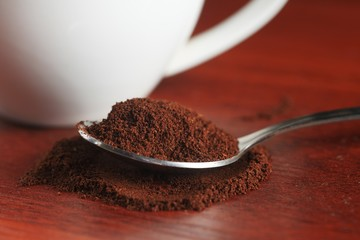 A spoonful of ground coffee lies on the table. Against the backdrop of a cup. Dark kitchen In a low key. Close-up. Macro