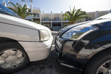 two closely bumper to bumper parking cars