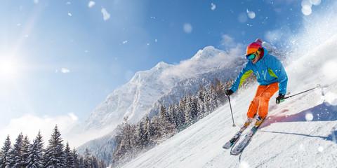 Skier on piste running downhill in beautiful Alpine landscape. Blue sky on background.