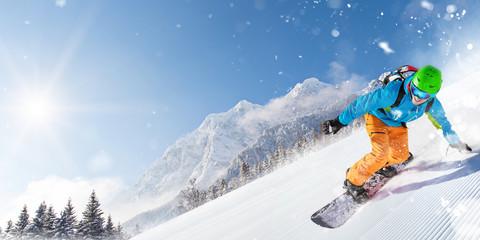 Snowboarder on piste running downhill in beautiful Alpine landscape. Blue sky on background.