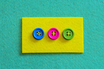 Different ways to sew buttons to felt. Felt piece with bright buttons isolated on felt background. Stitch buttons for sewing projects with colorful thread. Top view